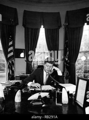 President John F. Kennedy addressing the AMVETS Convention in New York City by telephone from the Oval Office of the White House on August 23, 1962. - Stock Photo