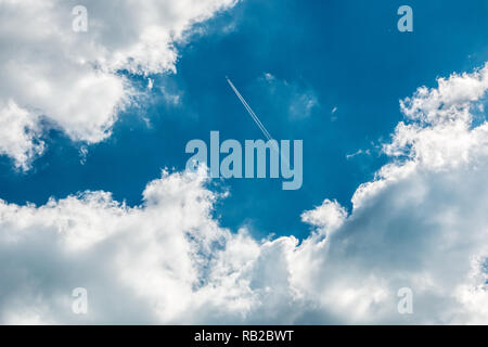 A plane above the clouds in the deep blue sky - Stock Photo