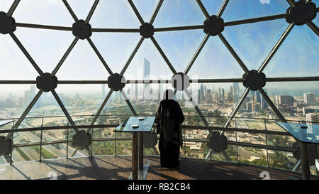 Woman looking at view of Kuwait City from viewing dome inside Kuwait Towers in Kuwait City, Kuwait - Stock Photo
