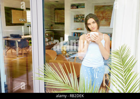 Portrait of young pretty woman wearing pajamas while standing with a cup of coffee behind window and dreaming. - Stock Photo