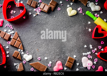 Valentine day baking concept, sweets and baking cooking background for Valentine`s day, with rolling pin, cookie cutters, sugar sprinkling, chocolate. - Stock Photo