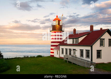 """Sunset by West Quoddy Head lighthouse, with its red and white stripes, referred to as the """"candy cane"""" lighthouse, in down east Maine, in New England. - Stock Photo"""