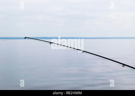 Boat fishing rod with the line over a beautiful cloudy seascape - Stock Photo
