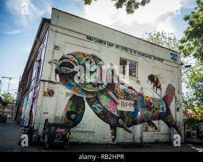 Berlin, Germany - May 21st 2018: Old industrial buildings decorated with colorful fish and bee graffiti, street arts - Stock Photo