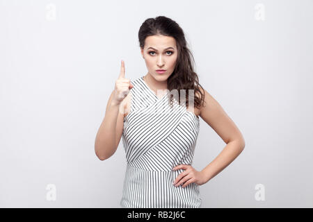 Portrait of serious beautiful young brunette woman with makeup and striped dress standing with warning sign, looking at camera with serious bossy face - Stock Photo