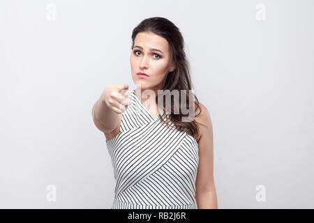 You. Portrait of serious beautiful young brunette woman with makeup and striped dress standing, looking and pointing at camera. indoor studio shot, is - Stock Photo
