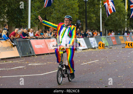 A man in a rainbow suit waving as he rides along The Mall with onlooking crowd, Brompton World Championships 2018, London, UK - Stock Photo