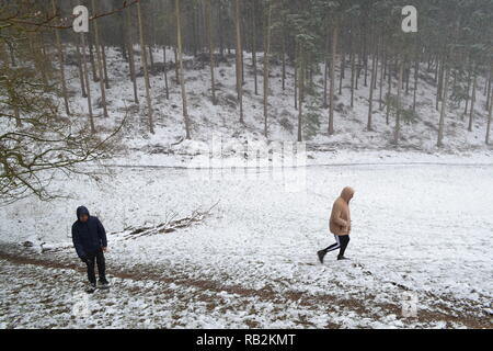 Young men walking in snow through Squerryes Park between Westerham, Hosey Common and Chartwell in Kent. March 2018 - Stock Photo