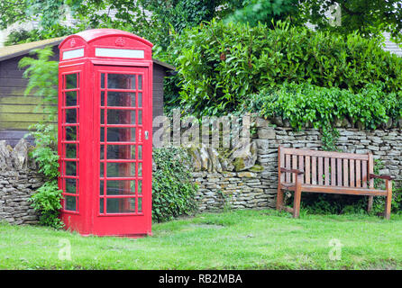 Red classic telephone box by a wooden bench in a village common, English rural countryside . - Stock Photo