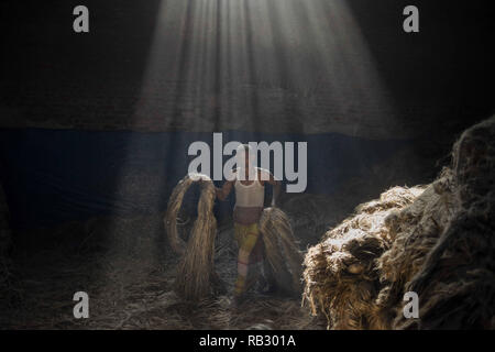Narayanganj, Bangladesh. 6th Jan, 2019. A jute mill worker seen walking with jute in his hands while sun-rays enter through the rooftop at the plant.Bangladesh is known for its Jute. In recent years Bangladesh and many other countries considered jute as the new possibility of replacing many daily goods and making bags out of jute to replace plastics. Credit: Ziaul Haque Oisharjh/SOPA Images/ZUMA Wire/Alamy Live News - Stock Photo