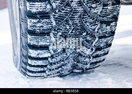 The car tire in the snow close up. Car tracks on the snow. Traces of the car in the snow. Winter tires. Tyres covered with snow at winter road - Stock Photo