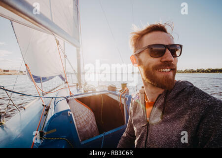Captain of the yacht wearing sunglasses in a race on a river or sea at sunset - Stock Photo