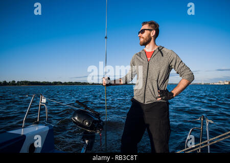 Young man wearing sunglasses standing on yacht stern and enjoying perfect autumn day under sails - sailing holidays concept - Stock Photo