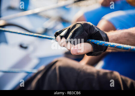 Close up of sailor winds aroung rope by using handle for coiling. He works with both hands. Young man stands on yacht. He is strong - Stock Photo