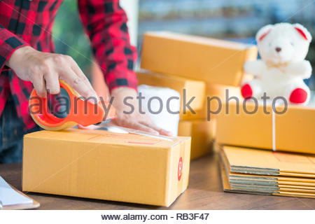 Shipping shopping online ,young start up small business owner writing address on cardboard box at workplace.small business entrepreneur SME or freelan - Stock Photo