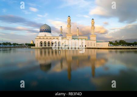 Beautiful Kota Kinabalu City Mosque reflected in lagoon during dusk sunset blue hour. - Stock Photo