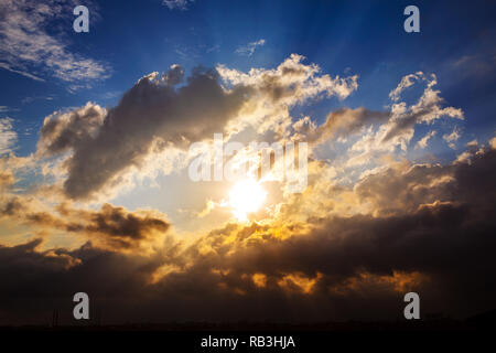 Rays of the sun at sunset among the clouds before the storm over city silhouette. Istanbul - Turkey - Stock Photo