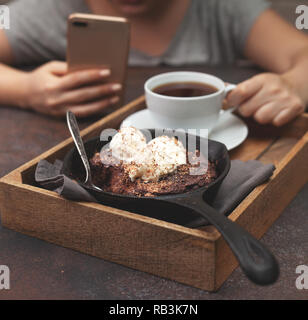 brownie with vanilla ice cream in a pan, a cup of coffee on a brown background - Stock Photo