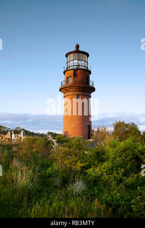 Light shines from the brick tower of Aquinnah lighthouse as the sun sets on a summer day on the island of Martha's Vineyard. - Stock Photo