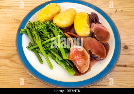 English lunch  dinner meal lamb chops boiled potatoes tenderstem broccoli red wine gravy and cranberry sauce blue edge white plate on a wooden table - Stock Photo