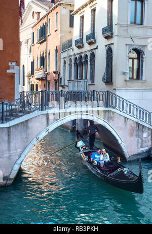 Couple taking a romantic gondola ride through the canals of Venice, Italy - Stock Photo