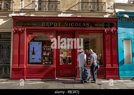 Two people looking in the window of Depot Nicolas, a wine merchants shop on Rue Saint-Louis en l'Île,Paris ,France - Stock Photo