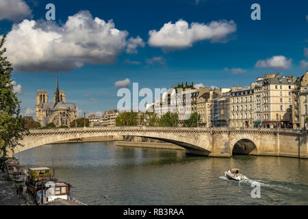 Pont De La Tournelle spans the River Seine with Notre Dame Cathedral and Île Saint-Louis in the background  on a warm summers day ,Paris ,France - Stock Photo
