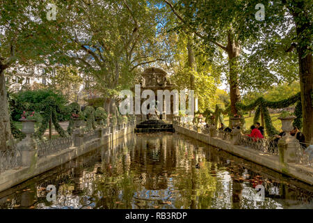 People admiring the The Medici Fountain or Fontaine de Medicis,a moumental fountain on a summer's day  in the Jardin du Luxembourg, Paris, France - Stock Photo
