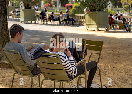 An attractive girl smoking a cigarette next to man reading a newspaper sitting on green metal chairs on a summers day in Jardin du Luxembourg ,Paris - Stock Photo