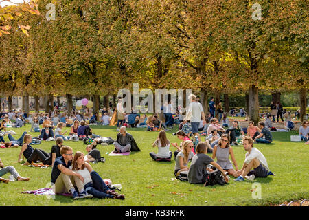 People sitting on the lawn at Jardin Du Luxembourg Gardens enjoying the summer sunshine ,Paris - Stock Photo