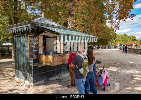 A line of People queueing at a refreshment kiosk on a summers day to buy refreshments from the kiosk vendor  in Jardin du Luxembourg ,Paris,France - Stock Photo