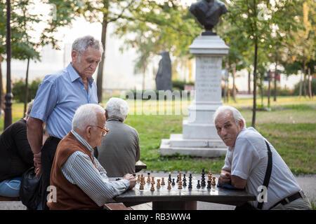 BELGRADE, SERBIA - JULY 11, 2018: Old senior men playing chess in a park of Kalemegdan fortress, in Belgrade, Serbia. Kalemegdan is one of the main la - Stock Photo