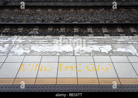 A faded and worn 'Mind the Gap' sign on the platform of a train station with the train rails in the background - Stock Photo