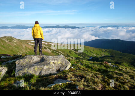 Alone tourist in yellow jacket stay on rock on high mountains. - Stock Photo