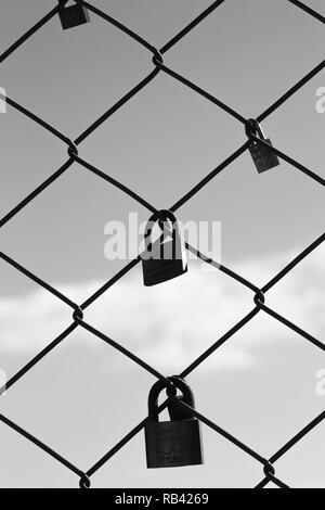 Black and white photography of weding padlocks on the fence of Santa Justa elevator, Lisbon, Portugal - Stock Photo