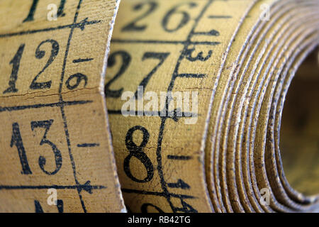 Old measuring tape isolated on white background, close-up - Stock Photo