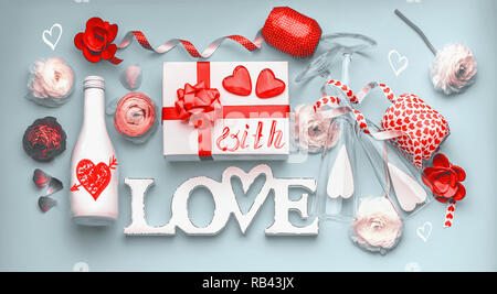 Valentines day layout . Festive composition of love made with flowers, gift box and red bow, bottle of champagne with glasses, hearts and party access - Stock Photo