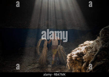 Narayanganj, Bangladesh. 6th Jan 2019. A jute mill worker seen walking with jute in his hands while sun-rays enter through the rooftop at the plant. Bangladesh is known for its Jute. In recent years Bangladesh and many other countries considered jute as a new possibility to replace many daily goods, notably making bags out of jute to replace plastics Credit: SOPA Images Limited/Alamy Live News - Stock Photo