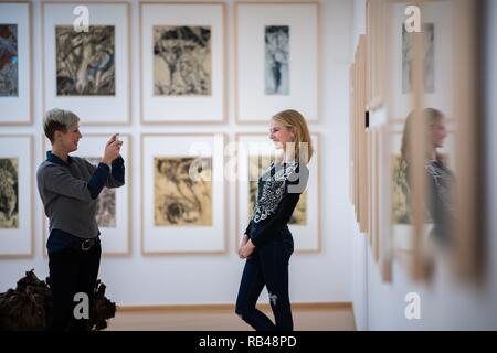Oldenburg, Germany. 18th Dec, 2018. Greta Schwarz (r) and Vivia Budrowitz are standing on a wall in the Horst Janssen Museum in Oldenburg with pictures by the artist Horst Janssen, taking a mobile phone photo. (about dpa 'Museums want to rediscover old artists' from 07.01.2019) Credit: Mohssen Assanimoghaddam/dpa/Alamy Live News - Stock Photo