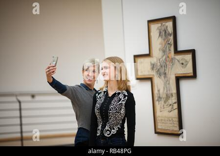 Oldenburg, Germany. 18th Dec, 2018. Greta Schwarz (r) and Vivia Budrowitz stand in front of the painting 'Das Problem der Menschen (Es ist ein Kreuz)' by the artist Horst Janssen from 1981 at the Horst-Janssen-Museum Oldenburg, and make a selfie of themselves. (about dpa 'Museums want to rediscover old artists' from 07.01.2019) Credit: Mohssen Assanimoghaddam/dpa/Alamy Live News - Stock Photo