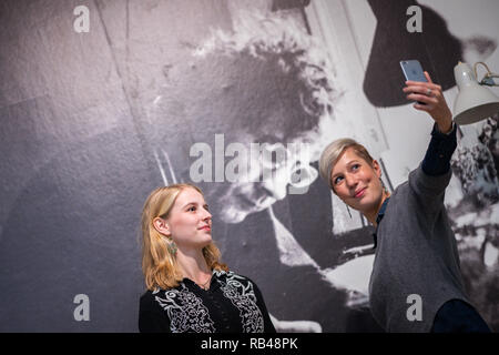 Oldenburg, Germany. 18th Dec, 2018. Greta Schwarz (l) and Vivia Budrowitz stand in front of a mural in the Horst-Janssen-Museum Oldenburg in which the artist Horst Janssen is depicted, making a selfie with a mobile phone (to dpa 'Museums want to rediscover old artists' from 07.01.2019). Credit: Mohssen Assanimoghaddam/dpa/Alamy Live News - Stock Photo