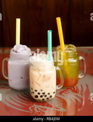 from left to right: taro smoothie, black milk tea with honey boba, honeydew green tea with strawberry popping boba on a table in a Chinese restaurant - Stock Photo