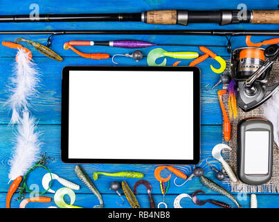 Fishing rod, tackles and fishing baits, reel on wooden board background with tablet computer isolated white screen, empty space for text - Stock Photo