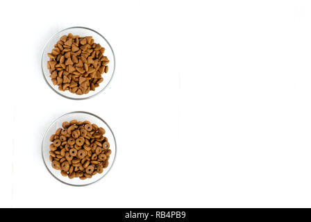 Dry cat food poured into a glass bowl on a white background - Stock Photo