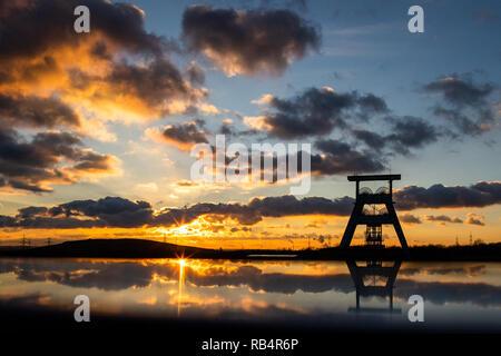 Der Förderturm der Zeche Ewald spiegelt sich in einem Geländer, während die Sonne am Horizont untergeht. - Stock Photo