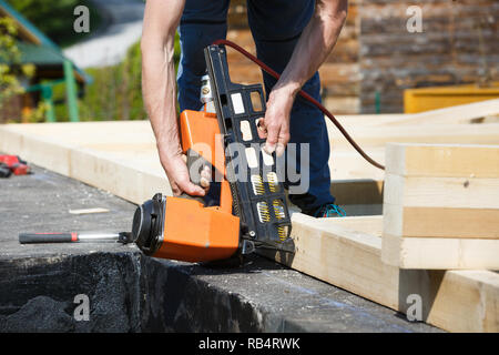 Professional carpenter using pneumatic nail gun on construction site. Occupational hazard, professional machinery, building industry concept. - Stock Photo