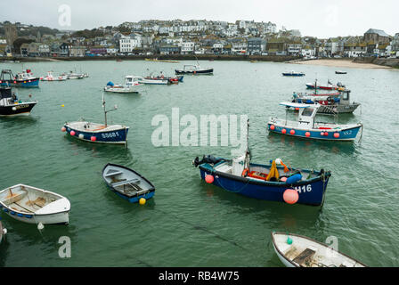Small fishing boats and pleasure craft moored in the harbour at St Ives with the historic town in the background. - Stock Photo