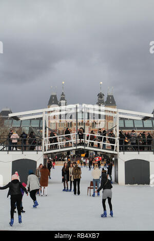 Skaters on ice rink in Museum Square, Amsterdam, in December - Stock Photo