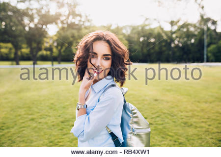 Portrait of cute brunette girl with short hair walking on sunset in park. She wears blue shirt and bag. She is smiling to the camera. - Stock Photo