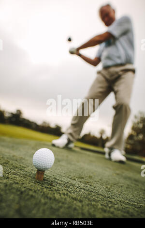 Golf ball on tee with male player practising a shot at driving range. Focus on golf ball on tee with golfer taking a shot. - Stock Photo